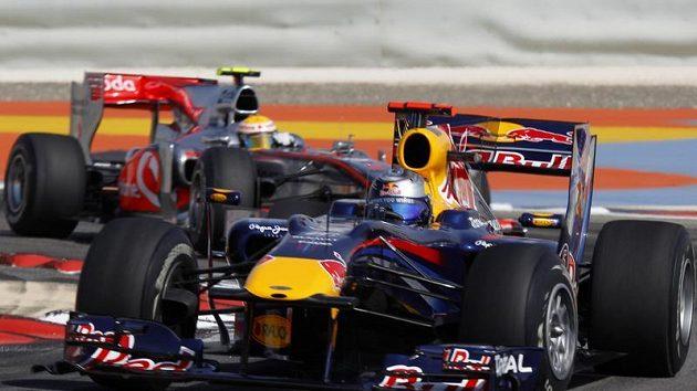 Lewis Hamilton s mclarenem jede za Sebastianem Vettelem ze stáje Red Bull při kvalifikaci na GP Bahrajnu.