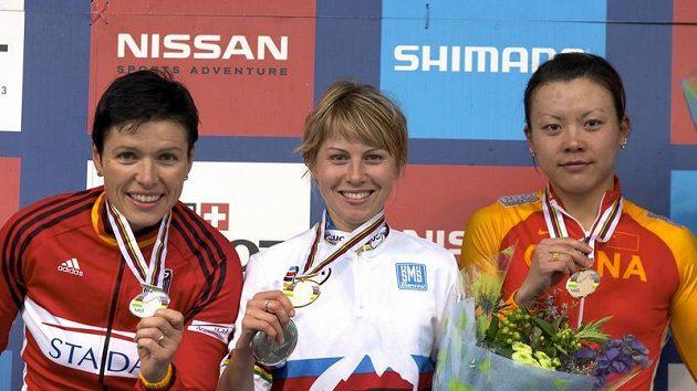 Ruská cyklistka Irina Kalenťjevová (uprostřed) ukazuje svou zlatou medaili ze závodu horských kol na MS ve skotském Fort Williamu v cross country. Vlevo je stříbrná Němka Sabine Spitzová, vpravo pak Ťing Ťing-wang z Číny.