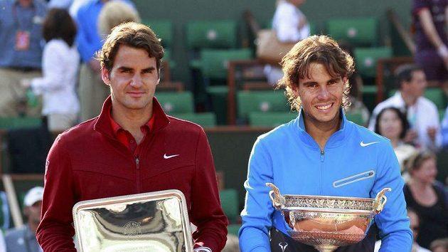Vítěz Roland Garros Rafael Nadal (vpravo) a poražený finalista Roger Federer s trofejemi.