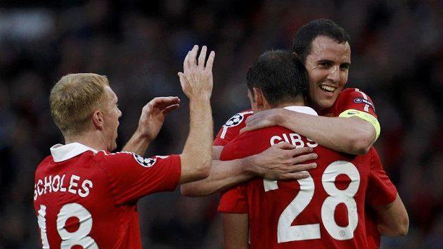 Fotbalisté Manchesteru United Paul Scholes (vlevo) a John O´Shea blahopřejí svému spluhráči Darronu Gibsonovi k brance.