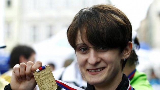 Martina Sáblíková se chlubí medailí, kterou získala za účast v Pražském mezinárodním maratónu.
