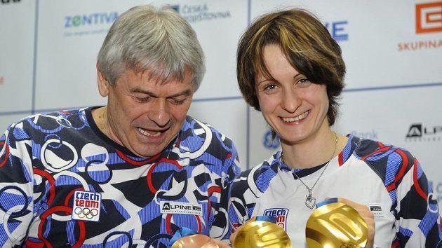 Martina Sáblíková a trenér Petr Novák ukazují v olympijské vesnici medailovou žeň.