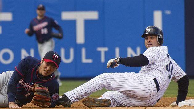 Cujoši Nišioka z Minnesoty (vlevo) se svíjí po ataku Nicka Swishera z New Yorku Yankees