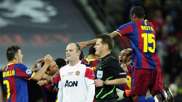 Zklamaný Wayne Rooney v kontrastu s radujícími se hráči Barcelony po konci finálového zápasu Ligy mistrů.