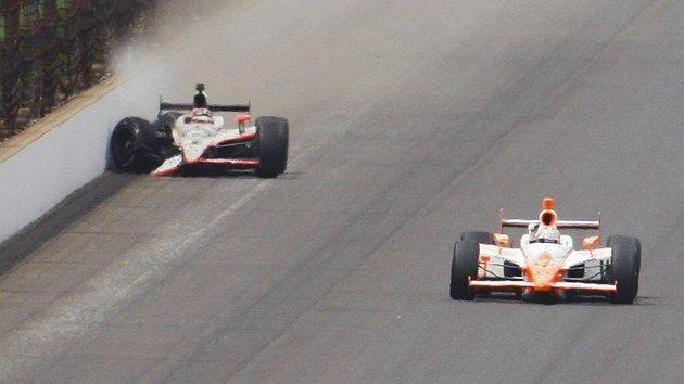 Rozhodující moment závodu 500 mil Indianapolis. Vedoucí JR Hildebrand (vlevo) rozbil těsně před cílem vůz a pro vítězství si jede Dan Wheldon.
