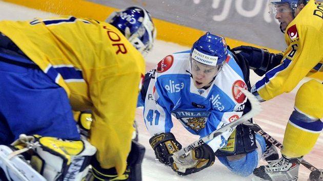 Finský hokejista Antti Pihlström padá před brankářem Švédska Stefanem Livem.