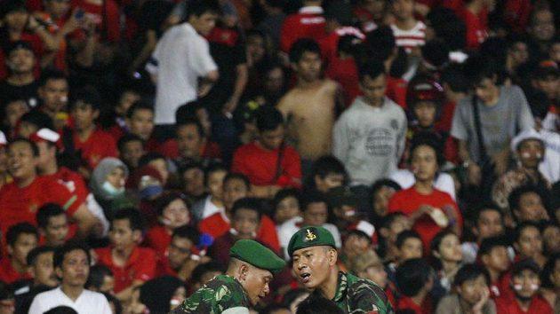 Vojáci se snaží dostat chlapce do bezpečí během fotbalového utkání v Jakartě