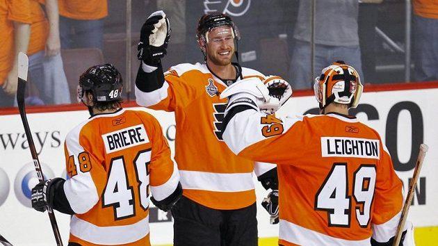Hokejisté Philadelphie Danny Briere (vlevo), Jeff Carter (uprostřed) a brankář Michael Leighton se radují z vítězství nad Chicagem ve finále Stanley Cupu.