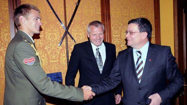 Ministr obrany Alexandr Vondra (vpravo) propůjčuje hodnost nadporučíka skifaři Ondřeji Synkovi.
