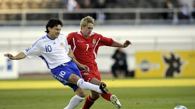 Fin Jari Litmanen (v bílém) v souboji s Davidem Edwardsem z Walesu