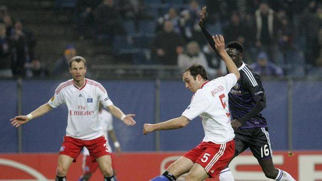 David Rozehnal v dresu Hamburku (v pozadí) sleduje svého spoluhráče Jorise Mathijsena, jak střílí v utkání proti Anderlechtu.