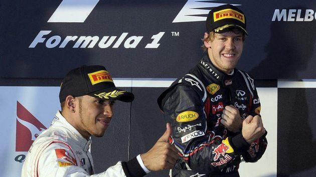Budoucí parťáci? Pilot McLarenu Lewis Hamilton (vlevo) křepčí se Sebastienem Vettelem z Red Bullu na stupních vítězů v australském Melbourne.