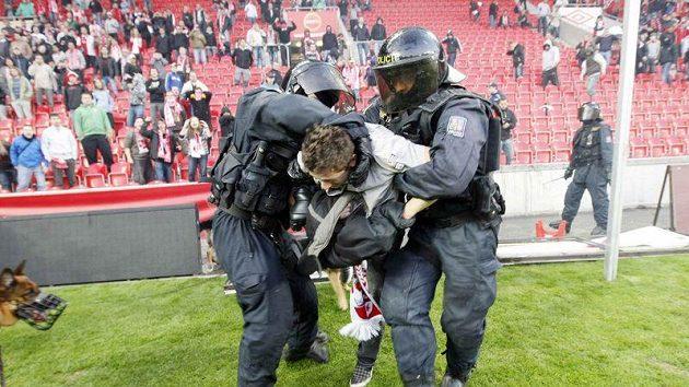 Policisté pacifikují jednoho z fanoušků Slavie při protestech v Edenu.