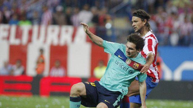 Obránce Atlétika Tomáš Ujfaluši (vpravo) fauluje hvězdu Barcelony Lionela Messiho.