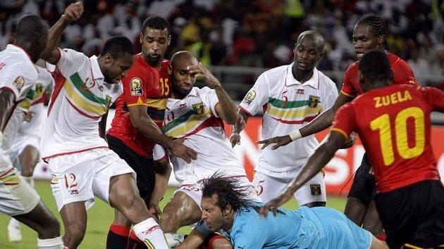 Velká skrumáž před brankářem Angoly Fernandesem Carlosem Albertem (v modrém).