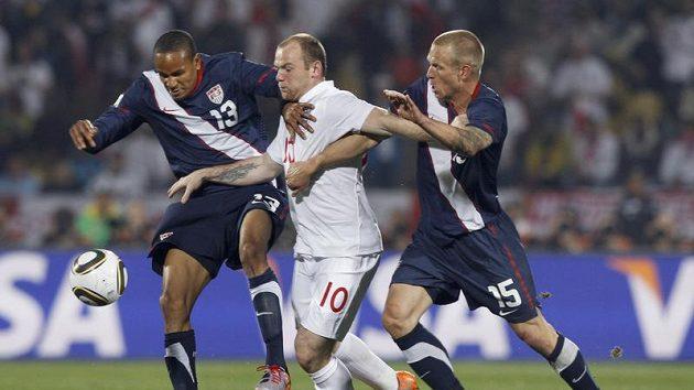 Anglický útočník Wayne Rooney (uprostřed) se snaží prosadit mezi Američany Jayem DeMeritem a Ricardem Clarkem.