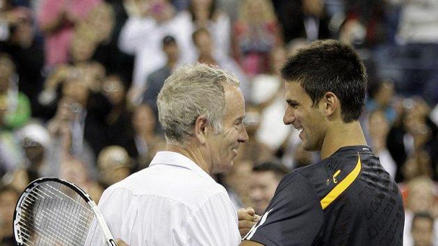 Tenisová legenda John McEnroe (vlevo) a současný tenista Novak Djokovič se zdraví nad sítí.