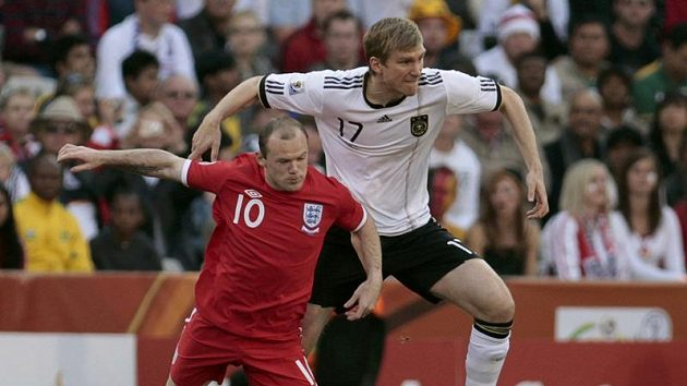 Angličan Wayne Rooney (v červeném) v souboji s Němcem Perem Mertesackerem.