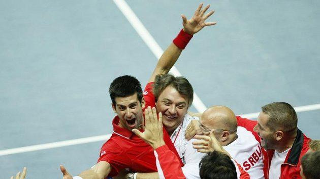Srbský tenista Novak Djokovič v objetí svých spoluhráčů a členů daviscupového týmu po postupu přes Chorvatsko.