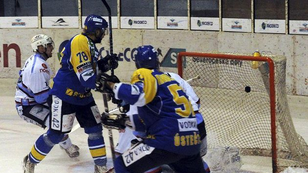 Ústecký Robin Hanzl (druhý zleva) střílí Chomutovu třetí gól svého mužstva.