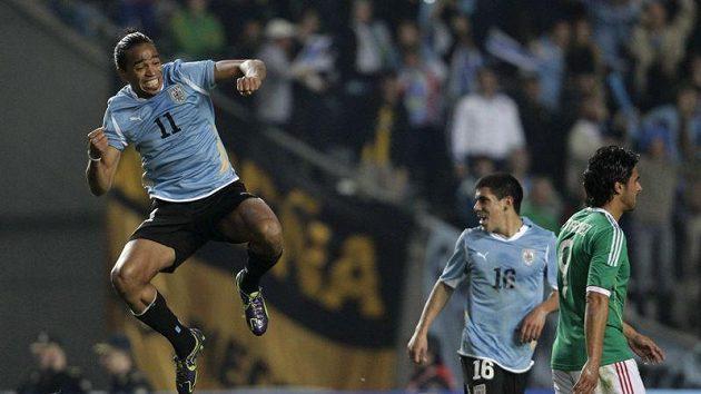 Alvaro Pereira z Uruguaye (vlevo) oslavuje vstřelený gól do sítě Mexika.