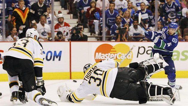 Brankář Bostonu Tim Thomas padá do střely Burrowse z Vancouveru ve finále NHL