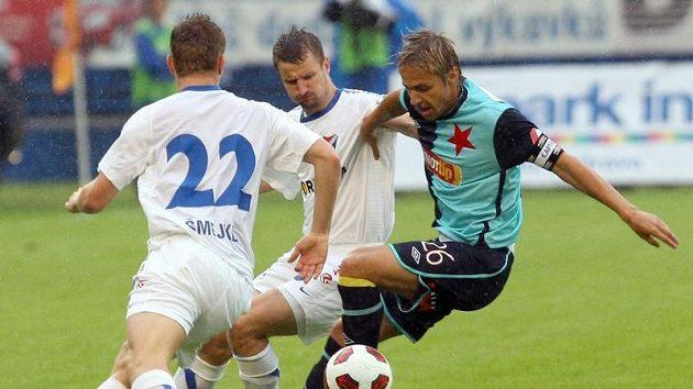 Zdeněk Šmejkal a Tomáš Frejlach z ostravského Baníku bojují s Jaroslavem Černým ze Slavie v utkání na Bazalech.