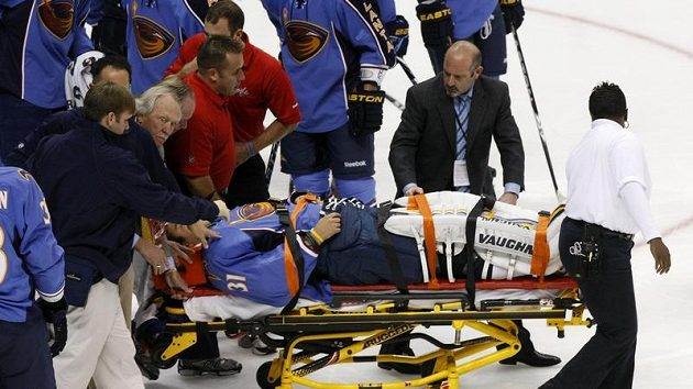 Brankář Atlanty Ondřej Pavelec je v bezvědomí odvážen z ledu na nosítkách.