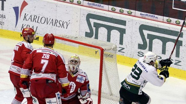 Karlovarský Lukáš Pech (vpravo) se raduje z gólu do sítě Třince. Brankář Peter Hamerlík se spoluhráči Danielem Semanem (vlevo) a Lukášem Zíbem jen přihlížejí. Nakonec se ale z výhry radovali oni.