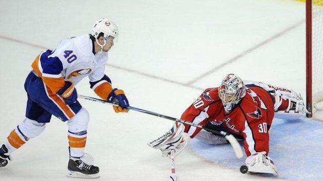 Český brankář Washingtonu Michal Neuvirth (vpravo) zastavuje průnik Michaela Grabnera z NY Islanders.