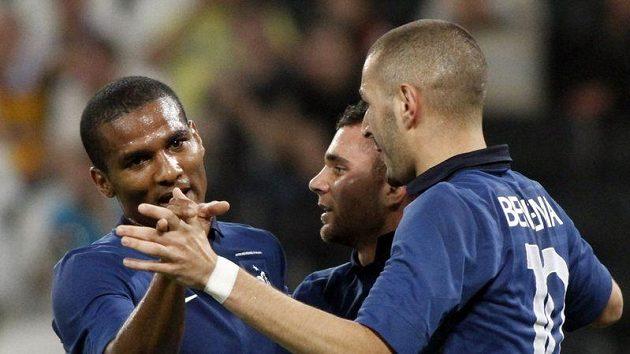 Francouzští fotbalisté Marvin Martin (uprostřed), Florent Malouda (vlevo) a Karim Benzema slaví gól proti Ukrajině.