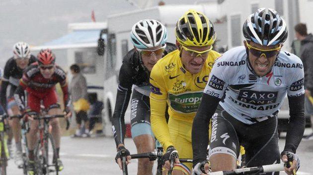 Alberto Contador (vpředu) se snaží v dešti roztrhat peloton. Španělského cyklisty se snaží udržet majitel žlutého trikotu Thomas Voeckler a Andy Schleck.