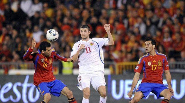 Čeští fotbalisté vědí, jak těžko se připravují Španělé o míč. Daniel Pudil se snaží prosadit mezi Busquetsem a Arbelou