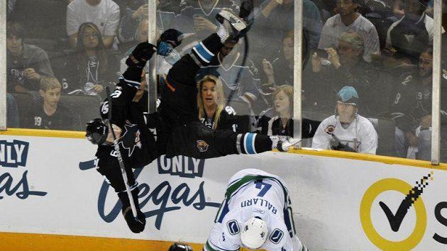 Hokejista San Jose Jamie McGinn letí vzduchem po zákroku Ballarda z Vancouveru
