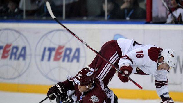 Petr Průcha z Phoenixu (vpravo) padá na led po střetu se Sandisem Ozolinšem z Dinama Riga.