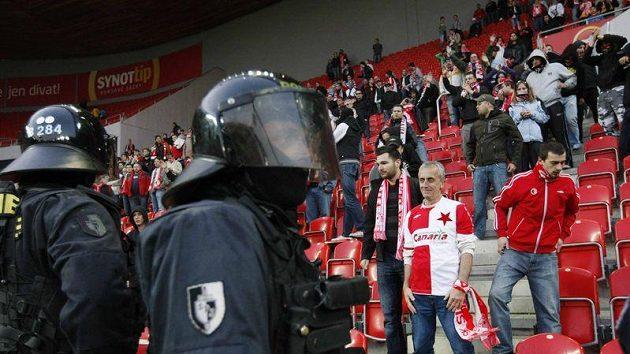 Policisté dohlíží na fotbalové fanoušky.