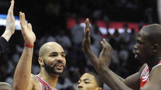 Basketbalisté Chicaga (zleva) Carlos Boozer, Derek Rose a Luol Deng oslavují koš vstřelený Atlantě.