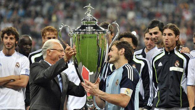 Franz Beckenbauer (vlevo) předává pohár Ikeru Casillasovi.