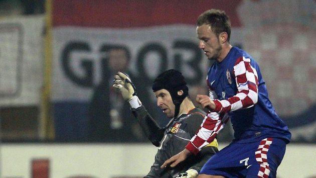 Brankář Petr Čech padá při snaze obehrát Chorvata Rakitiče.