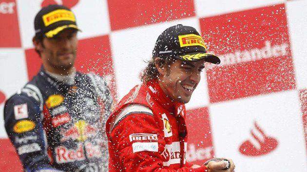 Fernando Alonso (vpředu) oslavuje s Markem Webberem, druhé, resp. třetí místo ve Velké ceně Německa. Alonso na vyhlášení přijel na Webberově monopostu.