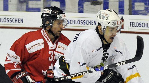 Karlovarský Petr Kumstát (v bílém) v souboji s Kanaďanem Curtisem Brownem v utkání Spenglerova poháru v Davosu.