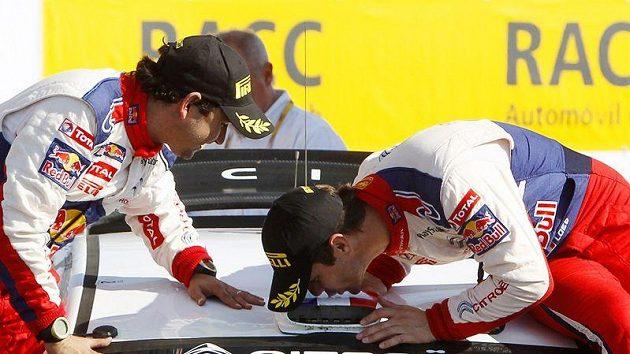 Sébastien Loeb (vpravo) vzdává hold svému vozu Citroën C4 WRC po triumfu v Katalánské rallye.