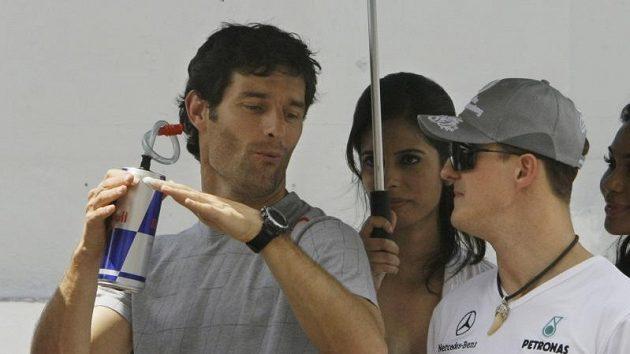 Mark Webber (vlevo) v rozhovoru s Michaelem Schumacherem.