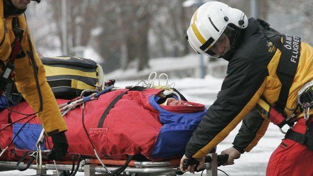 Záchranáři odvážejí těžce zraněného Hanse Gruggera ze sjezdovky.