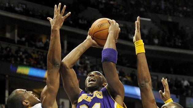 Kobe Bryant z Los Angeles Lakers (uprostřed) se snaží prosadit proti dvojici bránících hráčů z Denveru Nuggets Aaron Affalo (vlevo) a Shelden Williams.