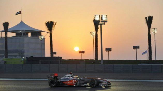 Jezdec McLarenu Lewis Hamilton na trati při západu slunce
