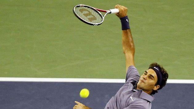 Roger Federer smečuje proti Johnu Isnerovi v zápase v Šanghaji.