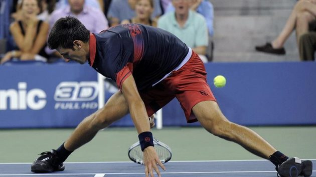 Novak Djokovič míjí míček v zápase s Petzschnerem