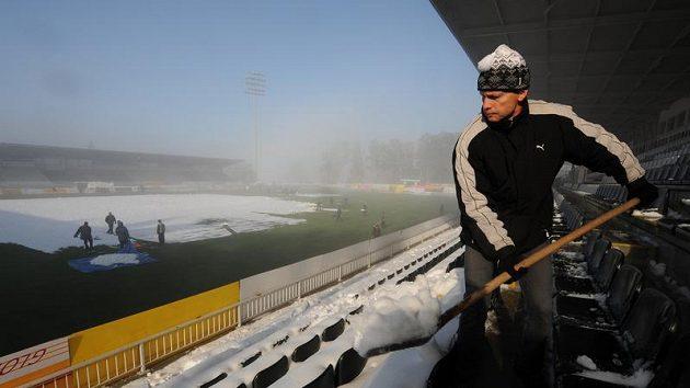 Jeden z vězňů odklízí sníh na stadiónu v Jablonci nad Nisou.