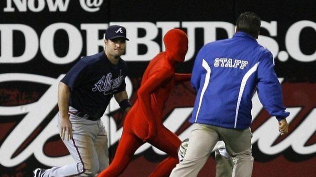 Baseballista Atlanty Matt Diaz (vlevo) se chystá zastavit nezvaného návštěvníka zápasu